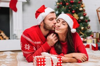 Man kissing woman near Christmas tree
