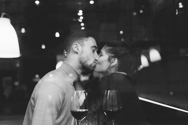 Man kissing woman near glasses of wine in restaurant