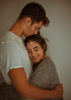 Man kissing woman on head