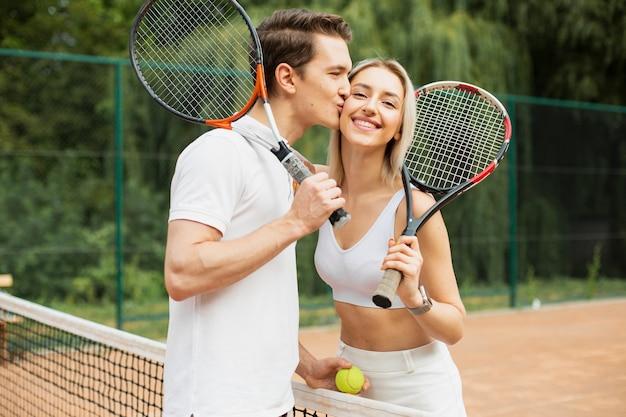 Мужчина целует женщину на теннисном корте