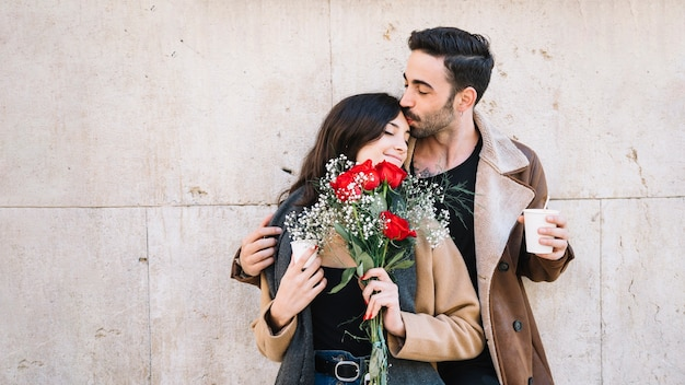Man kissing woman with bouquet