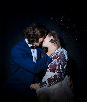 Man kissing young woman on party