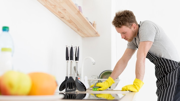 Man in kitchen cleaning