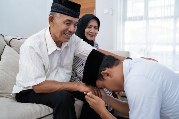Человек на коленях и целует руку своего родителя, прося прощения