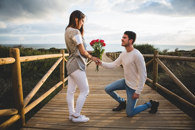 Man kneeling handing a bouquet of roses to a woman