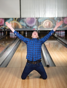 The man knelt in bowling after winning.