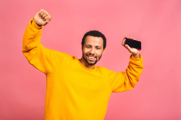 Man knowing that he became winner of something so rejoicing enjoying news information while isolated over pink
