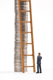 Man and ladder with coin stacks on white background