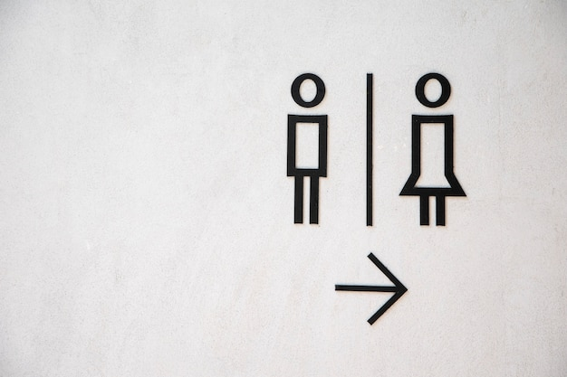 Man and lady toilet sign on white concrete wall background