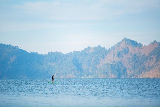 Un uomo sul lago cavalca una tavola da sup.