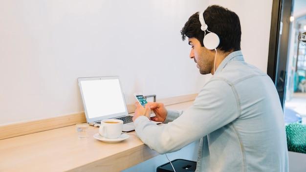 Man at laptoplooking atsmartphone
