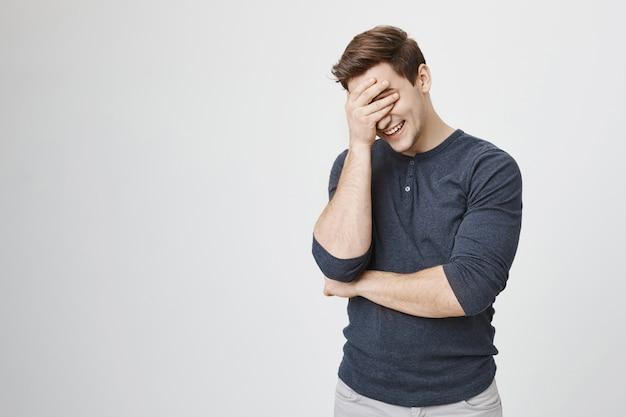 Мужчина смеется и закрывает лицо, чувствуя смущение