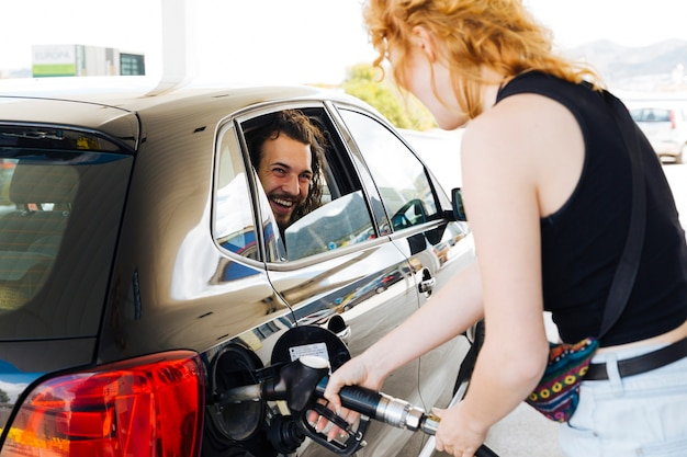 Man laughing out of car window with woman filling up car