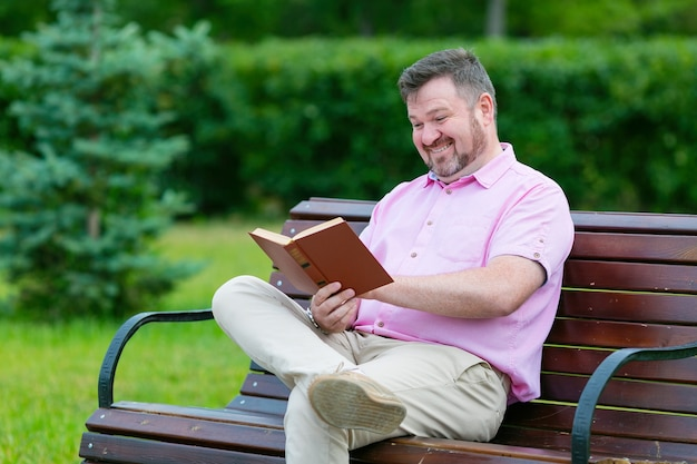 Человек громко смеется, читая книгу