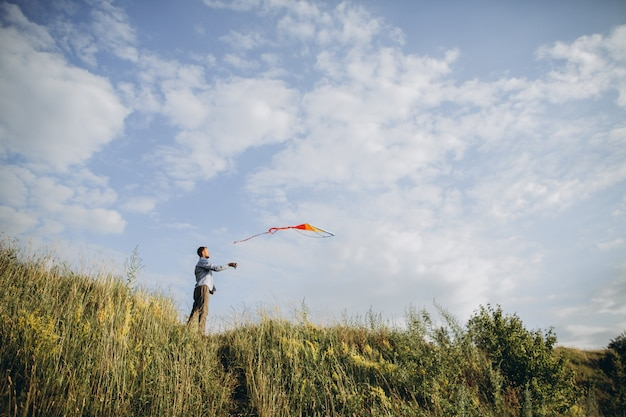 Man launching colorful air kite on the field