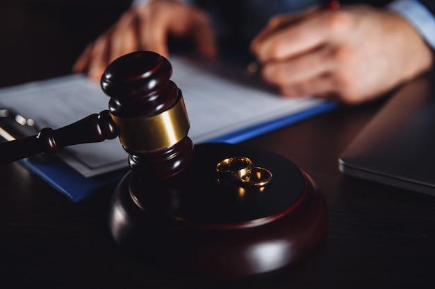 紙の契約で働く男性弁護士。机の上の木製のガベルとてんびん座。
