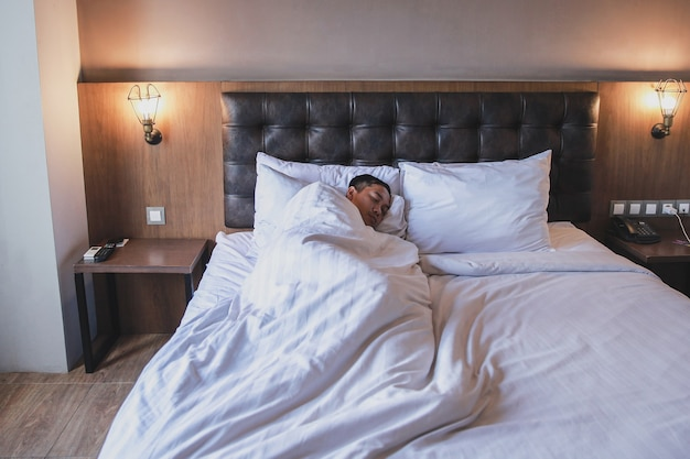 Man laying on bed covered with blanket while sleeping on white sheets