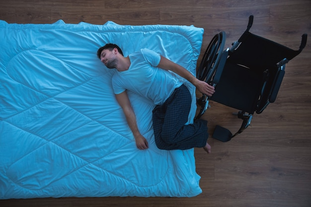 The man laying on the bed near a wheelchair. view from above, evening night time