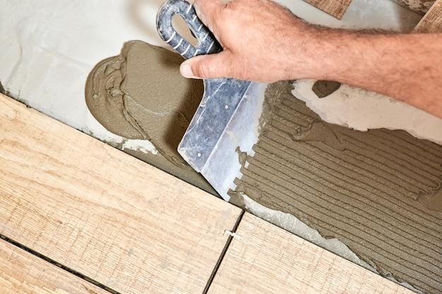 Человек укладывает керамическую плитку для пола. крупный план, выборочный фокус