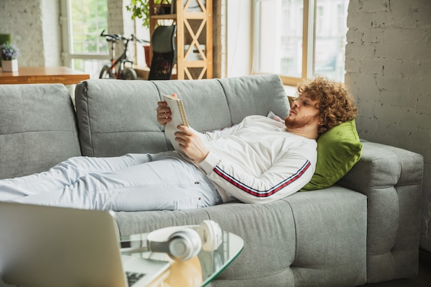 Man laying on the couch and reading a magazine
