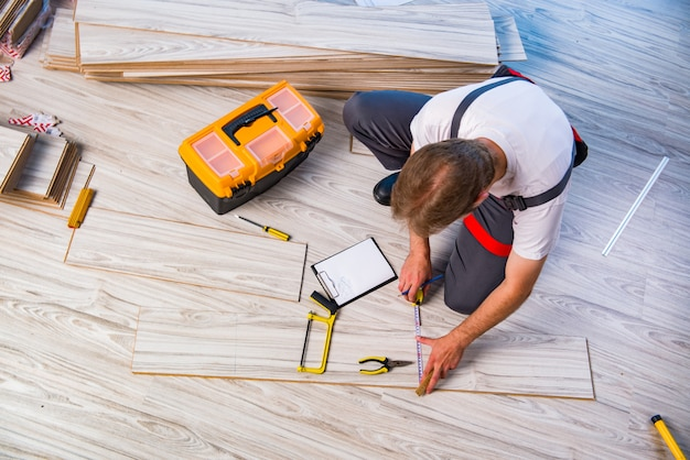Man laying laminate flooring in construction