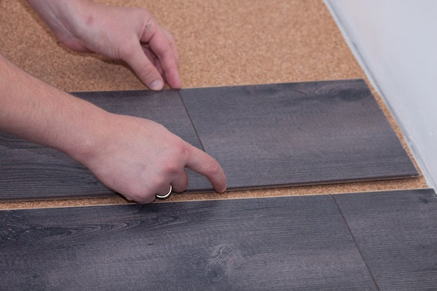 Man laying laminate flooring in a home