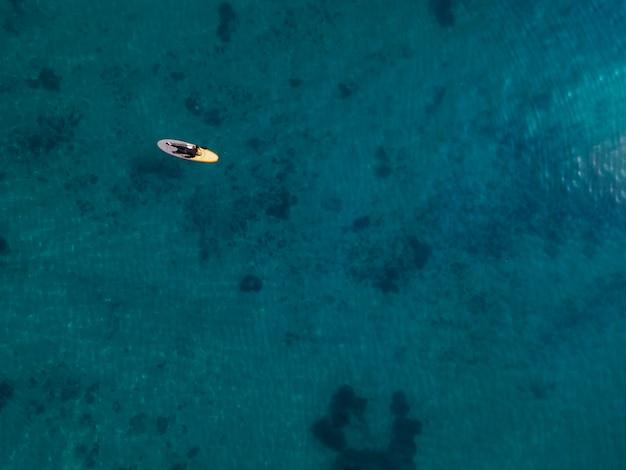 ビューの上のサーフボードに横たわっている男