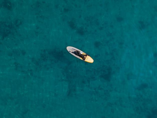 サーフボードの上面図に横たわっている男