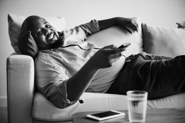 Uomo sdraiato e rilassante sul divano