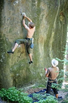 Man lead climbing on boulder securing carabiners and rope