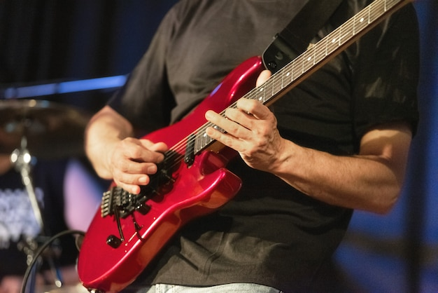 Man lead guitarist playing electrical guitar on concert stage.