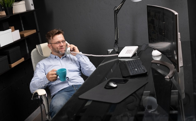 Man leaned back in his chair, drinking coffee and talking on landline