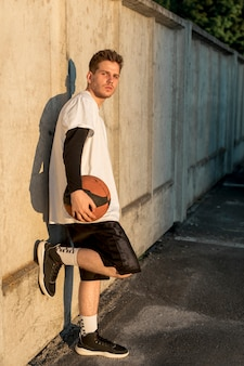 Man leaning against a wall with basketball