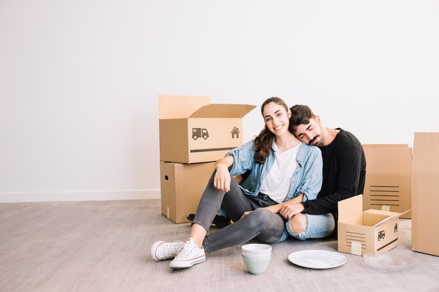 Man leaning against woman in front of moving boxes