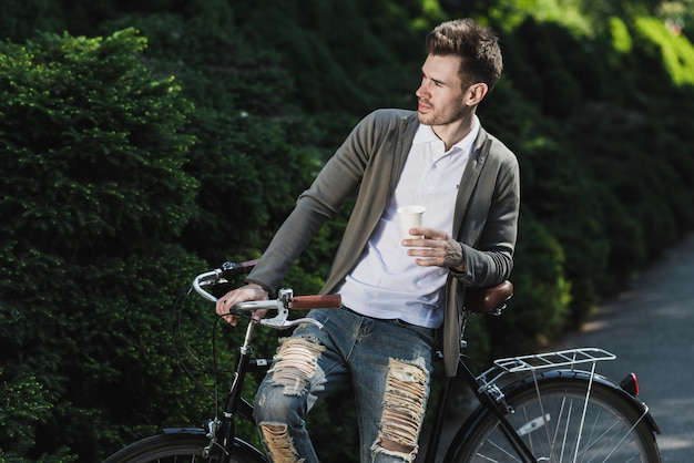 Man leaning on bicycle holding disposable coffee cup