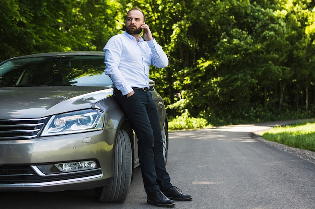 Man leaning on car talking on smartphone