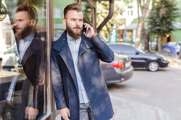 Man leaning on glass window talking on cellphone