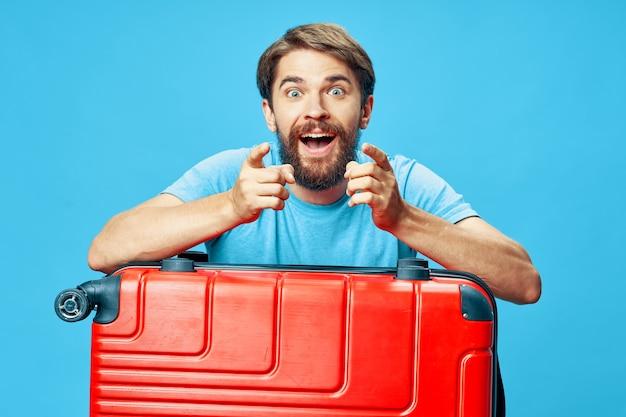 青い背景のトリミングされたビューの赤いスーツケースにひじをもたれている男