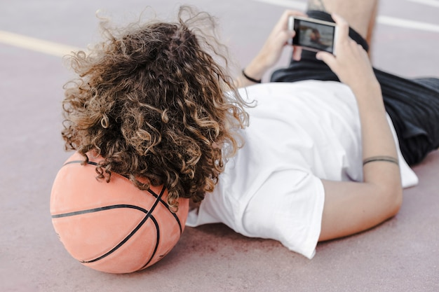 Man leaning his head on basketball using mobile phone