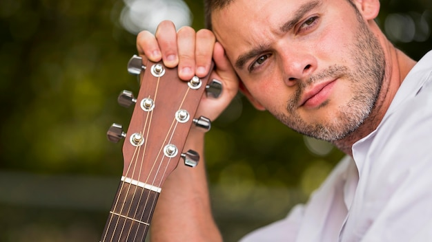 Man leaning his head on guitar headstock close-up
