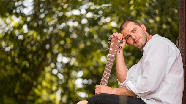 Man leaning his head on guitar headstock copy space