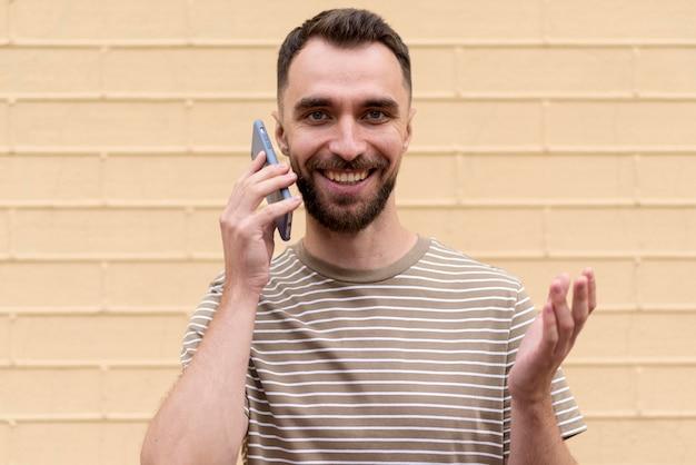 壁にもたれて電話で話している男性
