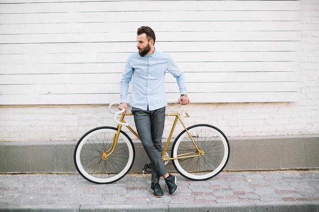 白い壁の近くの自転車に乗っている男