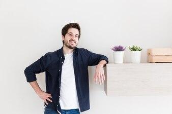 Man leaning on shelf near plants