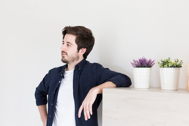 Man leaning on shelf and looking away