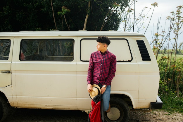 Man leaning on van with holding hat and backpack looking away