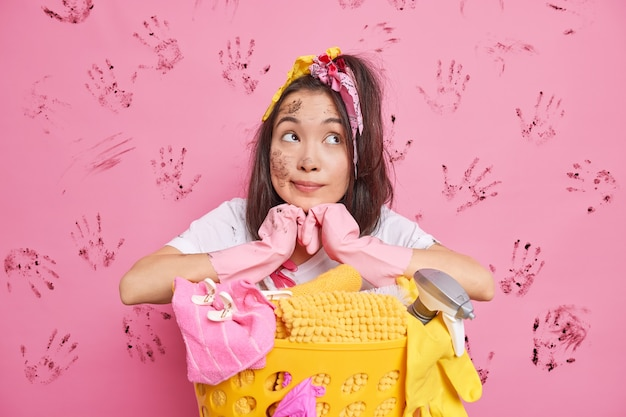 Man leans at laundry basket concentrated above has dirty look wears protective rubber gloves isolated on pink