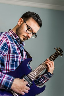 Man learn playing electric guitar at home