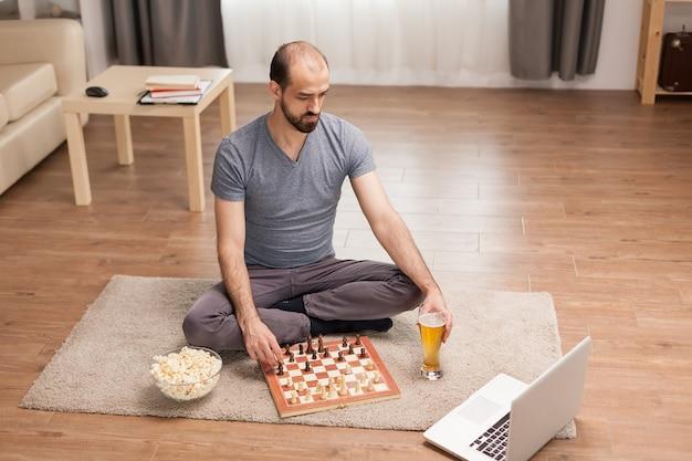 Мужчина учится шахматам от своего друга по видеосвязи во время covid-19.
