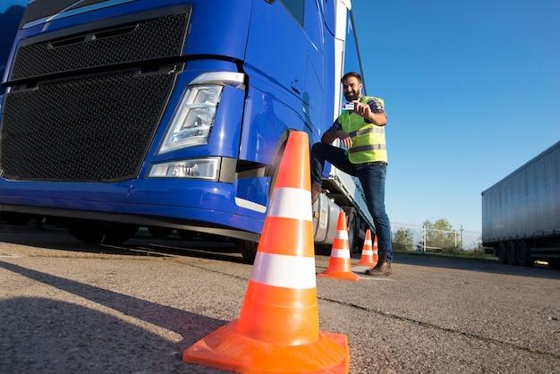 운전 학교에서 트럭을 운전하는 방법을 배우는 남자.